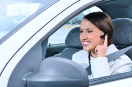 beautiful woman is safely talking phone in a car using a bluetooth headset